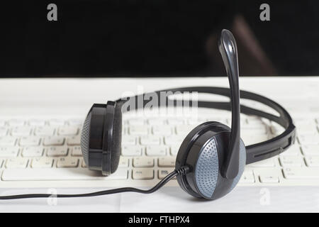 Headset with laptop computer keyboard.Communication concept - Stock Photo