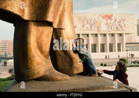 Young boy encouraged by his mother, kissing the feet of the statue of Enver Hoxha, the founder of the communist - Stock Photo
