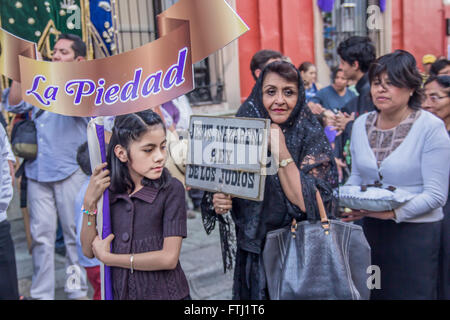 People at the Holy Friday procession in Oaxaca. The little girl is holding a placard which says 'Piety'. - Stock Photo