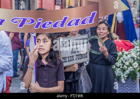 A little girl holding a placard saying 'Piety' at the Holy Friday procession in Oaxaca, Mexico. - Stock Photo