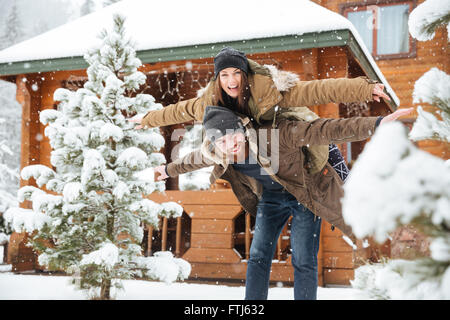 Cheerful attractive bearded man piggibacking his girlfriend and having fun in winter - Stock Photo