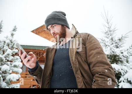 Serious bearded young man using smartphone standing outdoors in winter - Stock Photo