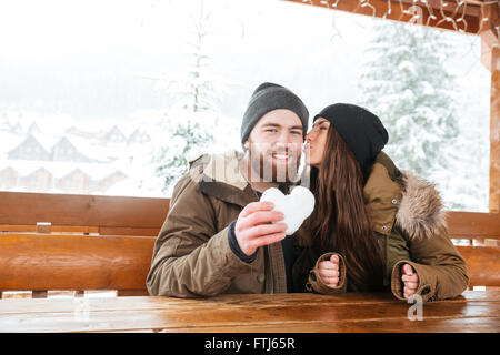 Happy young couple kissing in chalet patio and holding heart made of snow in winter - Stock Photo
