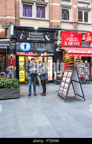 A couple checking their tickets from ticket booth in central London, UK - Stock Photo