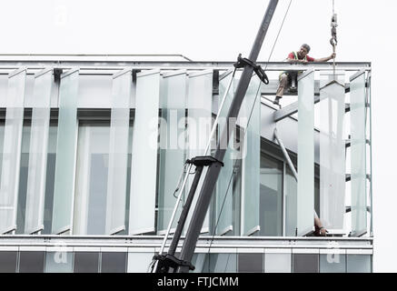 Workmen fitting external glass louvres on energy efficient new office block in Las Palmas, Gran Canaria, Canary - Stock Photo