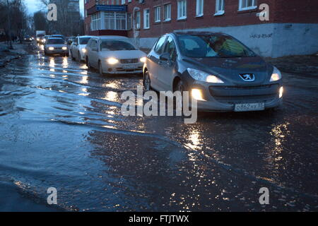 Omsk, Russia. 22nd Mar, 2016. Cars make their way through a flooded street in the city of Omsk. Omsk, with a population - Stock Photo