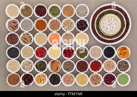 Large dried health food sampler in china bowls forming an abstract background over hessian. High in antioxidants - Stock Photo