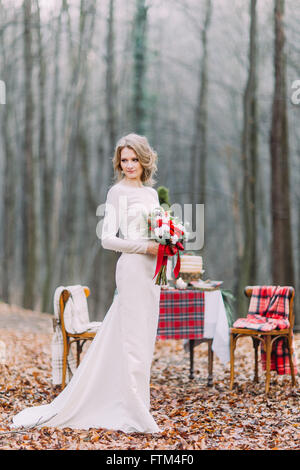 Beautiful blonde bride near christmas table in the forest - Stock Photo