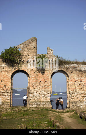 Tourists in the ruins of the old townhouse Lease Macedo on the shore of the Bay of Paranagua - Stock Photo