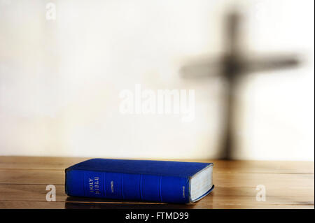 Old copy of Holy Bible lying on a table with shadow of a cross on background.