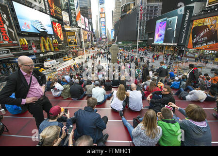 Young women sitting on steps in Times Square - central region of Manhattan - Stock Photo