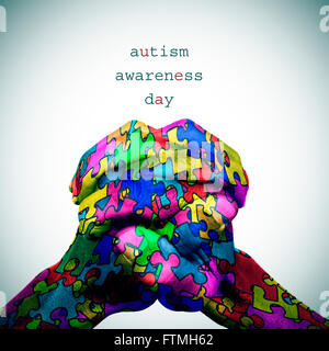 text autism awareness day and the hands of a man put together patterned with many puzzle pieces of different colors, - Stock Photo