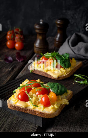 Toast for breakfast with scrambled eggs, cheese, cherry tomatoes, arugula and corn salad on rustic wooden background - Stock Photo