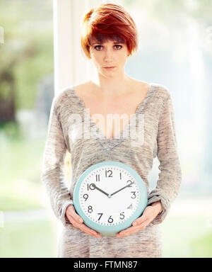 Woman stood holding a clock - Stock Photo