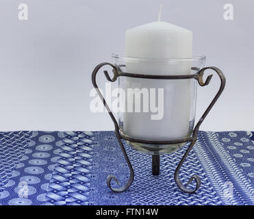 Close up of one white unlit candle against white and blue linen print background - Stock Photo