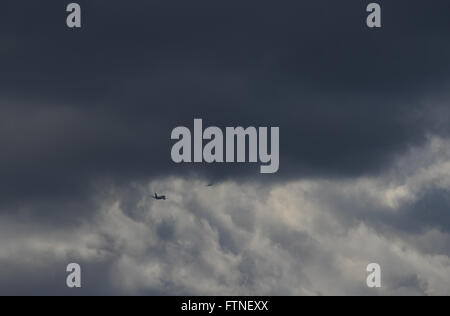 A boeing 737 follows another aircraft out of London's Heathrow Airport into a forbidding sky. - Stock Photo