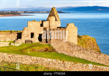 Fragment of ruins of Dunluce castle in County Antrim, Northern Ireland, UK, with the far view of  Portrush resort - Stock Photo