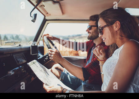 Side view of young couple using a map on a roadtrip for directions. Young man and woman reading a map while sitting - Stock Photo