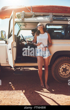 Young couple on car roadtrip. Man and woman taking a break from the road trip. Woman standing outside the car with - Stock Photo