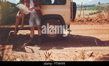 Cropped shot of couple with a map on road trip. Young man and woman with car stopping by a country road and reading - Stock Photo
