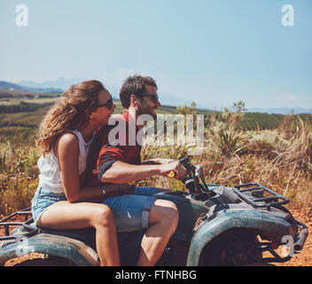 Side view of young man and woman riding on a quad bike on a summer holiday. Couple enjoying holidays on a quad bike - Stock Photo