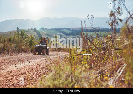 Young couple having fun on quad bike ride on a summer day. Young man driving the ATV girlfriend pointing at something - Stock Photo