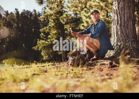 Portrait of senior caucasian man sitting outdoors in forest with a compass. Mature man hiking in nature looking - Stock Photo