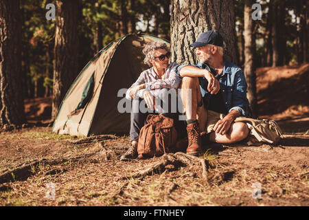 Portrait of happy senior couple sitting together under a tree on summer day. Mature man and woman near the tent, - Stock Photo