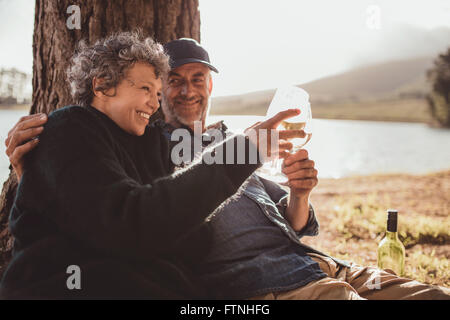 Portrait of happy senior couple sitting near a lake toasting with wine on camping. Woman and man drinking wine at - Stock Photo