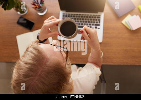 Overhead view of woman drinking coffee while sitting at her work desk at home office. - Stock Photo