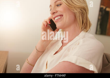 Close up of a happy woman talking on mobile phone. Caucasian female in conversation on cellphone. - Stock Photo
