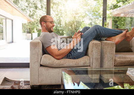 Side view image of a happy mature man using digital tablet while sitting on the sofa at home. Caucasian man relaxing on couch lo