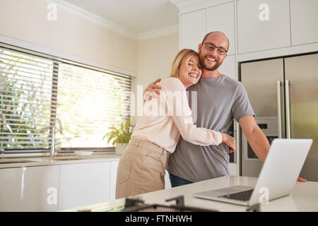 Indoor shot of loving couple in kitchen with a laptop. Mature man and woman embracing each other and smiling with - Stock Photo