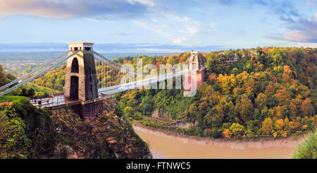 Clifton suspension bridge in warm light with autumn colours in Leigh Woods on the other side. - Stock Photo