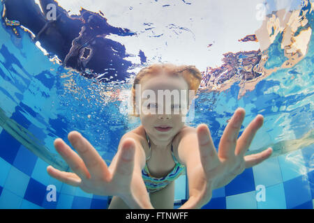 Funny face portrait of little baby girl swimming and diving underwater with fun in  pool. - Stock Photo