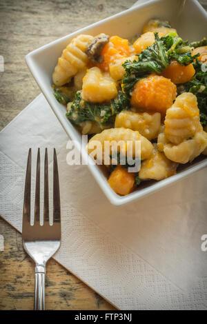 Vegetarian gnocchi dish with squash kale and mushrooms - Stock Photo