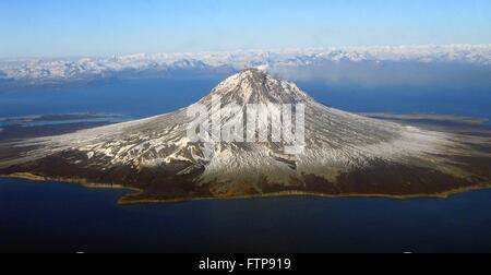 A small steam plume rises from the snow-covered lava dome at the summit of Augustine Volcano on Augustine Island - Stock Photo