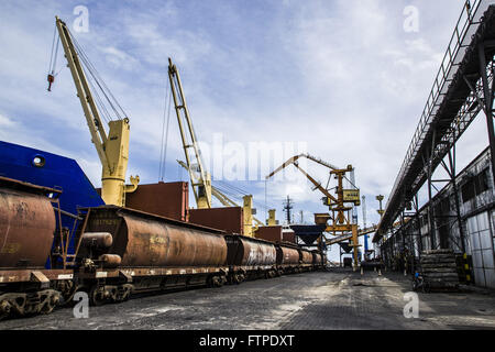 Train being loaded next to cargo ship in the port - Stock Photo