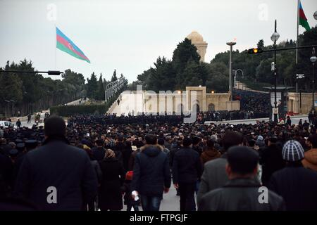 BAKU, AZERBAIJAN - JANUARY 20 2014 Crowds of cadets and mourners at monument in Baku, with Azerbaijani flags, on - Stock Photo