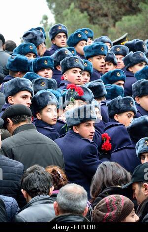 BAKU, AZERBAIJAN - JANUARY 20 2014 Cadets carrying red carnations at monument in Baku, on the anniversary of killings - Stock Photo
