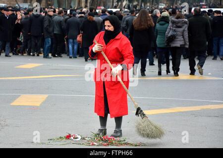 BAKU, AZERBAIJAN - JANUARY 20 2014 Woman in red coat sweeping up red carnations - Stock Photo