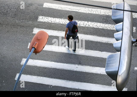 Man crossing crosswalk in the city center - Stock Photo
