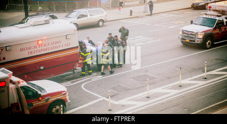 Emergency Medical Technicians  and FDNY firefighters transfer an obese in New York on Saturday, March 26, 2016. - Stock Photo