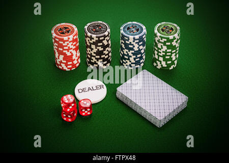 Casino chips, deck of cards, dealer chip and red casino dices lying on green casino table. - Stock Photo