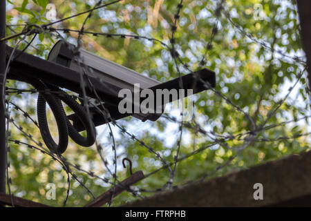 surveillance camera on a concrete fence with barbed wire - Stock Photo