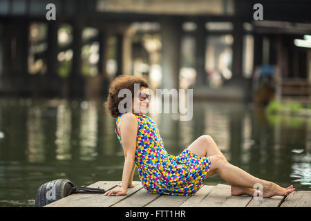 Fashionable young asian woman in sunglasses sitting on wooden river embankment. - Stock Photo