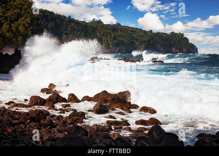 Large swells and heavy surf pound the lava shoreline at Laupahoehoe Point on the Big Island of Hawaii. - Stock Photo