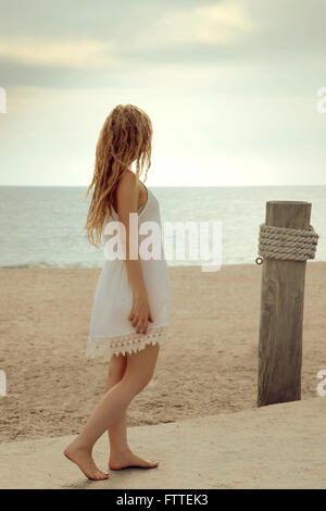 Blonde woman walking on beach - Stock Photo
