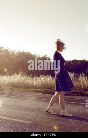 1950s young woman walking on street - Stock Photo