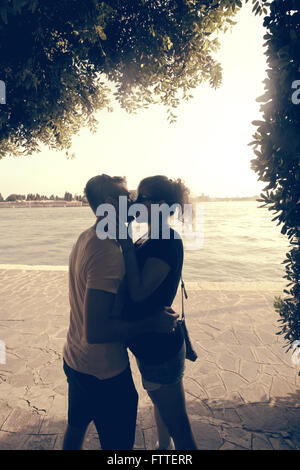Young couple kissing in the shade - Stock Photo